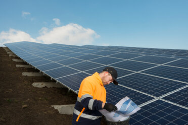 Engineer connecting solar panels on new solar farm, situated on former waste dump - CUF45327