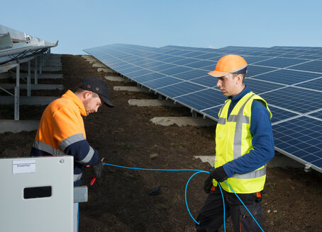 Engineers connecting solar panels on new solar farm, situated on former waste dump - CUF45330