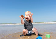 Toddler horrified with sea water on hands on beach - CUF45384