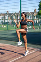 Young woman exercising in sports court - CUF45669