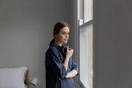 Portrait of woman having coffee by window - CUF45675
