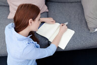 Woman sitting on floor writing in notepad - CUF45690