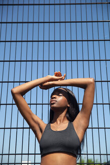 Young woman leaning against wire fence - CUF45792