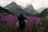 Woman looking out at mountain ranges, Glacier National Park, Montana, USA - CUF45897