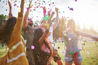 Five young adult friends throwing confetti mid air at Holi Festival - CUF45957