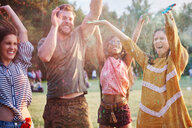Four young adult friends dancing and throwing coloured chalk powder at Holi Festival - CUF45960