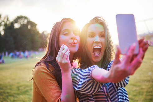Two young woman covered in coloured chalk powder taking selfie at Holi Festival - CUF45963