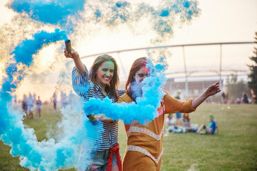 Two young women dancing with blue smoke bombs at Holi Festival - CUF45972