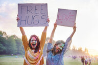 Young women dancing holding up love and free hug signs at Holi Festival - CUF45975