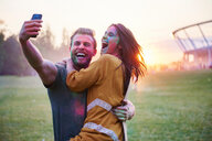 Young couple covered in coloured chalk powder taking selfie at Holi Festival - CUF45981