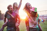 Two young couples covered in coloured chalk powder piggybacking at Holi Festival - CUF45984