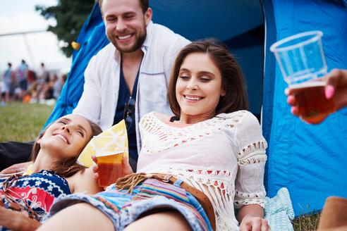 Friends sitting and enjoying music festival - CUF46014