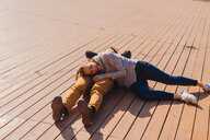 Couple relaxing on wooden decking - CUF46047