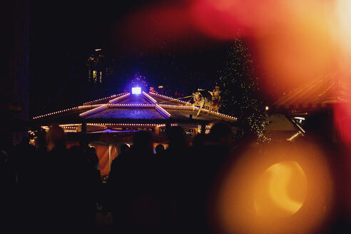 Germany, silhouettes of people at illuminated Christmas market - MMAF00618