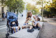 Mother sitting on bench playing with with her sons - AZOF00070