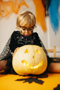 Portrait of little girl with painted face and fancy dress sitting on table with Jack O'Lantern pouting mouth - JRFF01880