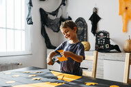 Smiling little boy cutting out for Halloween decoration at home - JRFF01886