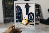 Man taking photo of Halloween decoration with digital tablet - JRFF01901