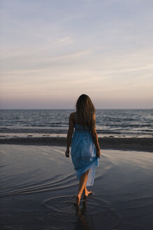 Back view of young woman wearing blue dress walking on the beach by sunset - MAUF01719