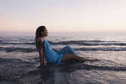 Young tattooed woman wearing blue dress sitting in water at seashore watching sunset - MAUF01722