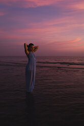 Young woman standing in front of the sea by sunset - MAUF01728
