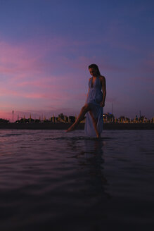 Young woman wearing summer dress standing in water at seashore by sunset splashing with water - MAUF01731