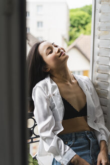 Smiling attractive young woman sitting at the window - AFVF01657