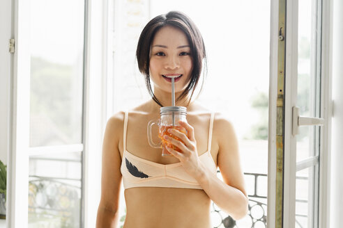 Portrait of attractive young woman wearing bra having a drink at the window - AFVF01675