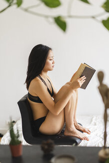 Attractive young woman in lingerie sitting on chair at home reading book - AFVF01681