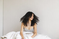 Young woman in bed shaking her head - AFVF01693