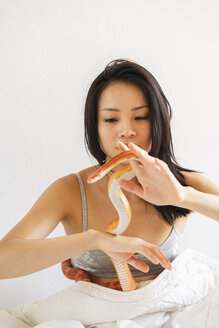 Young woman in bed with a snake - AFVF01699