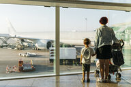 Spain, Barcelona airport, Mother and son waiting in departure area - JRFF01905