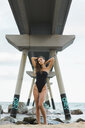 Portrait of beautiful young woman wearing swimsuit standing at the seafront - AFVF01724
