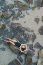Overhead view of beautiful young woman lying  on rock in the sea - AFVF01754