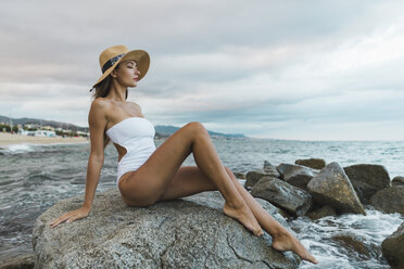Beautiful young woman wearing swimsuit and hat sitting on rock in the sea - AFVF01766