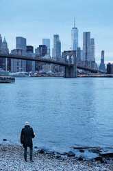 Man looking out over Brooklyn Bridge and Lower Manhattan Skyline from riverbank, New York, USA - ISF19693