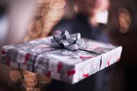 Boy handing over Christmas gift - ISF19828
