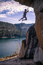Young male rock climber dangling on rope from rock face, High Sierras, California, USA - ISF19840