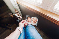 Mother holding photograph of twin baby girl and boy, personal perspective - ISF19858
