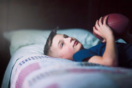 Boy on bed with american football - ISF19879