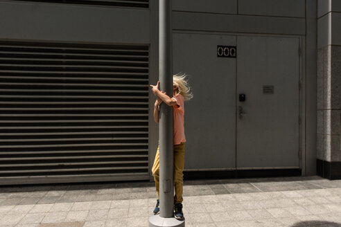 Boy hugging lamp post on day trip in Toronto, Canada - ISF19903
