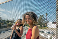 Two young women laughing on highway footbridge, Los Angeles, California, USA - ISF19969