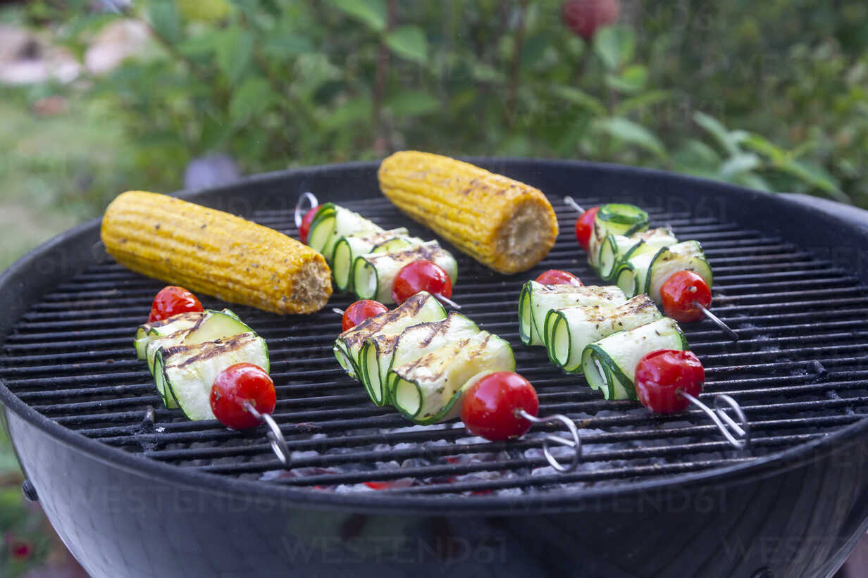Grilled vegetarian grill skewers, tomato, sheep cheese and zucchini slices, corn cobs on grill - SARF03943 - Sandra Roesch/Westend61