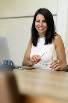 Portrait of smiling dark-haired woman using laptop at desk - HHLMF00526