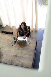 Overhead view of smiling woman using laptop at desk - HHLMF00535