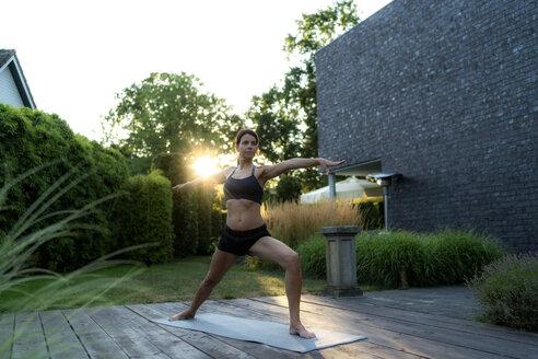 Woman practicing yoga in garden - HHLMF00550