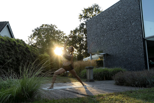 Woman practicing yoga in garden - HHLMF00553
