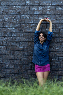 Smiling woman standing at brick wall stretching - HHLMF00556