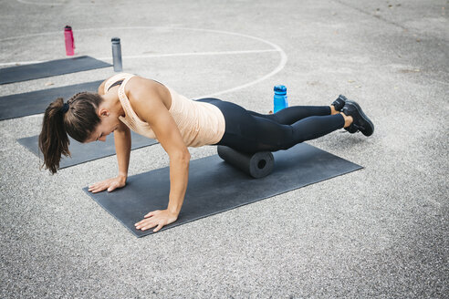 Young woman doing workout exercise with fascia roll outdoors - HMEF00026