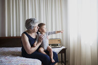 Grandmother sitting on bed with her grandson - AZOF00079